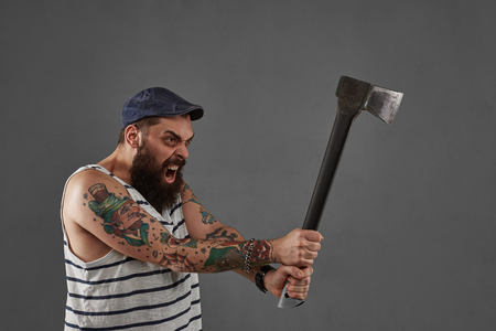 unleash: Aggressive tattoo big bearded man with ax. Shout person with open mouth. Businessman after hard work. Angry manager concept. Stock Photo