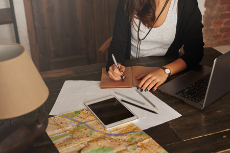 intend: Woman planning new trip. Girl write tourist notes at home. Tablet, laptop, city map on the table. Brighten effect. Girl learn the route in the new city. Loft interior with big wooden doors.
