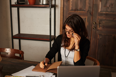 Latin pretty student work at home. Stylish beautiful woman with brunette hair in glasses write notes in notepad. Free space on the shelf for advertising products.
