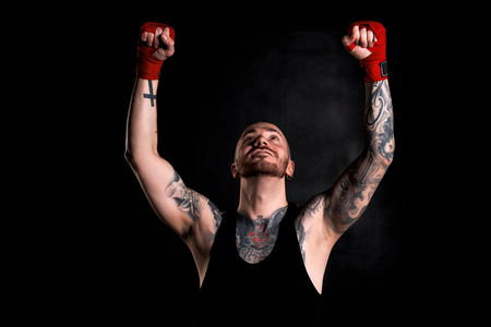 bandwagon: Victory concept. Fighter win the round of battle. Portrait of tattooed body guy in black t-shirt on dark background with red bandages.