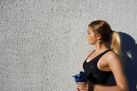 Profile portrait of blonde sporty girl with muscular arms having rest after intense cardio exercise outdoors, refreshing herself, drinking water out of plastic cup, feeling tired and exhausted
