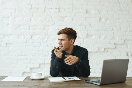 Attractive confident young recruiter sitting at office desk with open laptop computer, copybook and papers, looking sideways and pointing index finger at camera during job interview with applicant Фото со стока