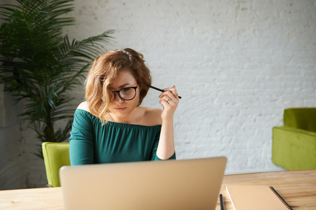 Young pretty journalist write new article about extreme competition for online magazine. Student girl search information for project or reading morning news after hot weekend in loft office interior