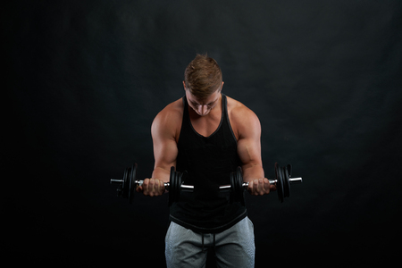 Hard trainig on biceps with dumbbels. Train strong body. Athletic exercises on black background. Front view on working gym trainer. Фото со стока