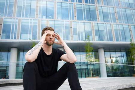 Depression concept of office manager. Stylish man sitting on steps and hold head by two hands. Guy have relax and planning new real business project after resolving problems. Male in black.