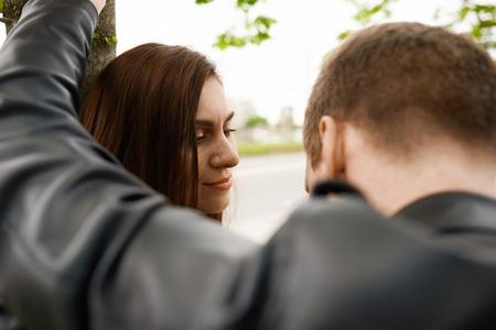 Breack up relationships 개념. 남자와 여자 ans를 말하는 도시에서 나무 근처 숙박. 화창한 날에 함께 걷기. 연인 커플은 주말을 보내고 있습니다. 다툼 후 불