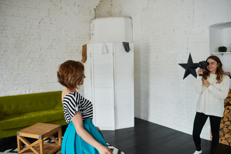 Candid shot of female photographer in white sweater holding camera taking pictures of happy young woman in beautiful clothing during fashion photo shoot in professional photographic studio interior Фото со стока
