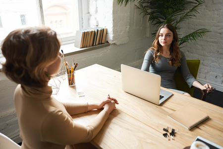 Beautiful confident young businesswoman sitting at her office desk and smiling while interviewing unrecognizable female candidate for personal assistant position. Recruitment and human resources