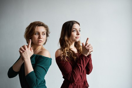 Studio shot of two young women friends having fun indoors, fooling around, posing at blank wall, holding fingers as if they are pistols, pretending to shoot, looking sideways with serious looks