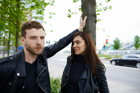Beautiful young couple having walk in city park. Handsome stylish unshaven male in leather jacket standing close to pretty female, leaning hand on tree and looking at camera with serious expression Фото со стока