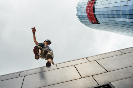 Stylish man experiencing virtual reality, using oculus goggles with head-mounted display, standing on edge of skyscraper, about to fall down. Gaming, 3d technology, cyberspace and entertainment Фото со стока