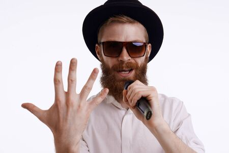 People, music, show and entertainment concept. Handsome stylish bearded showman or presenter wearing trendy hat and sunglasses performing on stage holding microphone, showing back of hand at camera Фото со стока