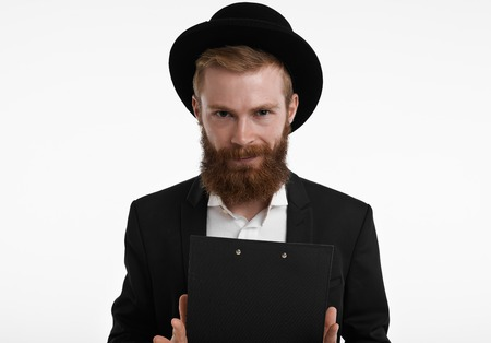 Its showtime. Studio shot of attractive bearded young man in stylish elegant black tuxedo and headwear looking at camera with mysterious smile, holding clipboard in both hands, ready to entertain you Фото со стока