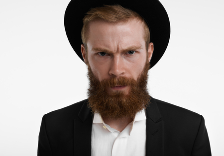 Headshot of grumpy young European hipster with fuzzy ginger beard frowning, having unhappy or angry expression on his face, feeling displeased and dissatisfied with something, wearing hat and suit