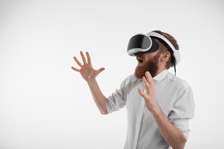 Profile picture of young bearded manager in formal shirt wearing virtual reality goggles, entertaining himself during break at office, exclaiming and gesturing as if interacting with someone