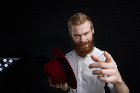 People, show and entertainment concept. Studio shot of macho man with fuzzy red beard and stylish haircut holding trendy hat and pointing finger at camera, presenting something or giving speech