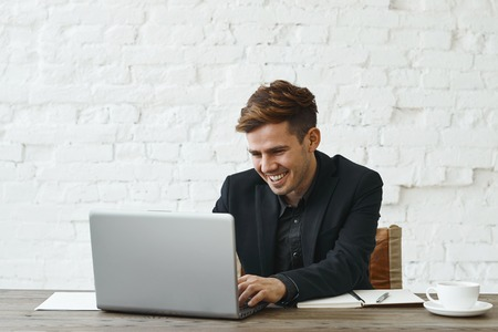 Stylish young European office worker in formal wear sitting in front of laptop pc, playing video games during lunch break, looking at screen with cheerful smile. Male employee working at office