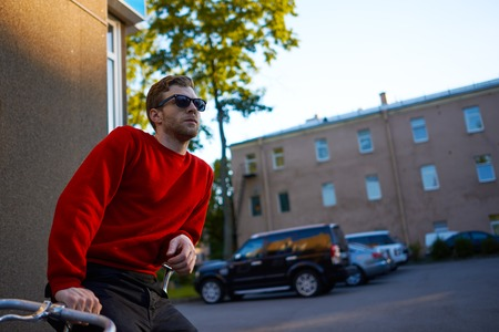 Urban portrait of confident bearded Caucasian hipster guy wearing red sweatshirt, black jeans and sunglasses leaning on his retro bicycle, relaxing after bike ride with empty street in background Фото со стока