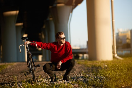 Handsome guy in trendy shades sitting in squatting posture on grass, holding his fixed gear bicycle, relaxing after long ride. People, leisure, hobby, active healthy lifestyle and transportation Фото со стока