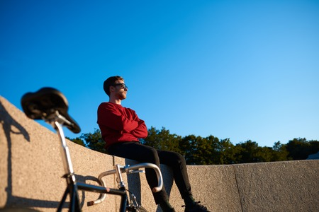 Outdoor shot of serious confident young hipster wearing shades sitting on concrete fencing with his fixed gear bike next to him, looking into distance, contemplating beautiful nature around him