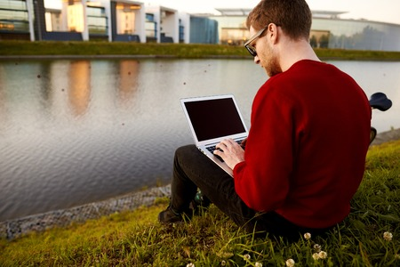 Rear view of stylish young male traveler sitting by the lake booking plane tickets online using free wi-fi on generic laptop computer with copy space blank screen for your advertising content
