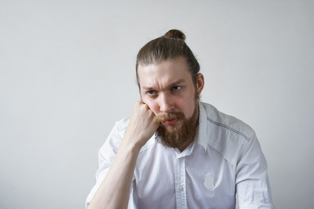 Sadness and boredom concept. Studio shot of unhappy young manager with hair knot and thick beard having upset and bored look, feeling tired and pissed off with boring working days at office Фото со стока