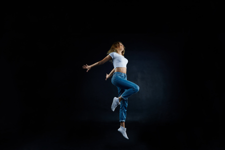Studio shot of beautiful young European woman dancer with slim flexible body practising indoors, sharpening her dancing skills, dressed in sensible clothing. People, hobby and active lifestyle concept