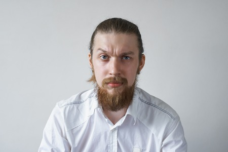 Headshot of displeased angry unshaven young employee staring at camera with grumpy and pissed off look, frowning, having bad mood, feeling dissatisfied and furious about something. Human emotions