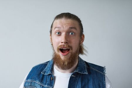 Headshot of excited astonished stylish young European man with thick beard and hair gathered in knot raising eyebrows and opening mouth widely in surprise and astonishment. Human reaction and attitude