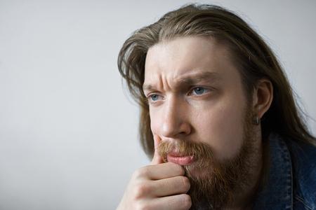 Gefrustreerde, nadenkende jonge Europese man met een vage baard met een peinzende uitdrukking op zijn gezicht, diep in gedachten, denkend aan de juiste oplossing tijdens het omgaan met een belangrijk probleem of probleem