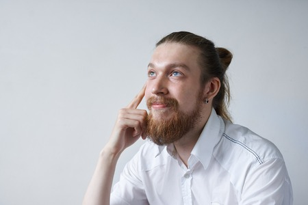 Attractive dreamy positive young male employee with thick beard and hair knot dressed in white formal shirt sitting in his office and looking up, daydreaming, planning summer vacations by the sea