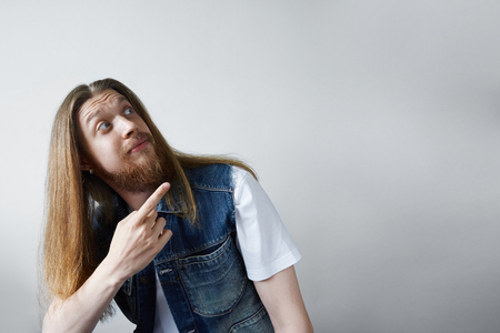 Indoor picture of funny unshaven young Caucasian man with long loose hair looking upwards and pointing index finger at grey blank studio wall with copy space for your text or promotional content Фото со стока