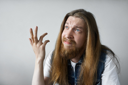 indignant: Headshot of emotional young Caucasian male with moustache and beard dressed casually looking up with indignant and frustrated expression, making a questioning gesture with hand. Body language
