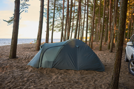 Family holidays, vacations, adventure, travel, activity and adventure concept. Picture of camping place with tent and white car on sandy deserted beach at nature park or forest by the lake or river