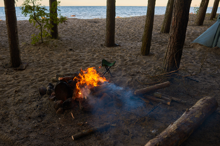 Outdoor summer shot of campsite with fireplace, camping tent in wild nature. Somebody set camp among trees in forest on beach by river or sea. Hiking, trekking, adventure and traveling concept