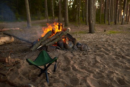 Camp fire blazing in wild nature surroundings witn no people around. Someone made up fire on deserted sandy beach to cook grilled meat and vegetables. Trekking, traveling and hiking concept Фото со стока