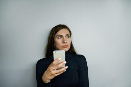 Attractive confident brunette woman wearing black turtle neck using messengers or browsing web sites on mobile phone, posing isolated against blank grey wall background with copy space for your text
