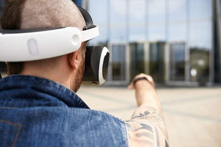 Rear view of brutal bearded European male hipster with tattoos and Mohawk hairstyle standing outdoors wearing futuristic 3d goggles with head mounted display and pointing finger at modern building