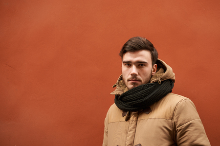 Waist up shot of attractive confident young European male with beard and mustache dressed in winter clothes, staring at camera with serious look. People, lifestyle, seasons and clothing concept Фото со стока