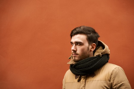 Outdoor picture of handsome unshaven young man wearing jacket and scarf while feeling cold, standing outside building with orange wall with copy space for your text or promotional information Фото со стока