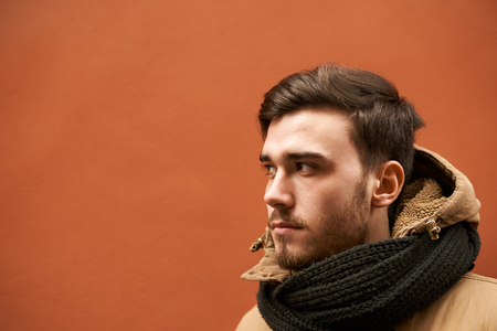 Close up portrait of serious confident young Caucasian male student dressed in warm clothing while spending time outdoors, waiting for bus to commute to work. Autumn, winter and cold weather