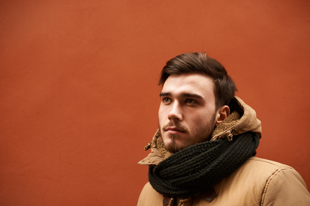 Headshot of stylish young Caucasian man wearing warm jacket and scarf standing outdoors at blank orange wall, looking up with thoughtful dreamy expression. People, modern lifestyle and fashion