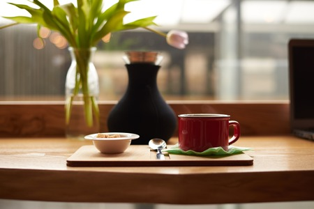 Mock up of hot coffee latte or cappuccino in red cup and white bowl with cane sugar cones resting on wooden table with decorative plants by the window glass in cozy restaurant during breakfast
