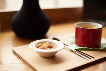 Detailed close up shot of red mug of coffee or tea, bowl with brown sugar cubes and cutlery on wooden tray on cafe table by the window. Drinks, food, leisure and beverage concept. Selective focus