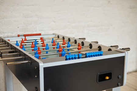 Detailed close up picture of football table with metall rods with red and blue foos men players figures in empty room with white blank copyspace wall for your advertisement or promotional content