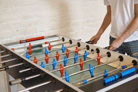 People, leisure, entertainment, fun and tabletop games concept. Unrecognizable male kicker enjoying foosball match, moving foosball rods with blue men figures back and forth. Selective focus