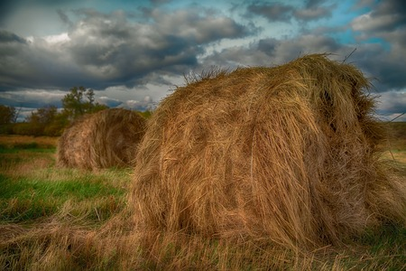 rebelling: hay stack in a summer field. Beautiful landscape with storm clouds