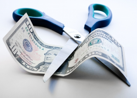 Scissors cutting through dollar note on white background photo