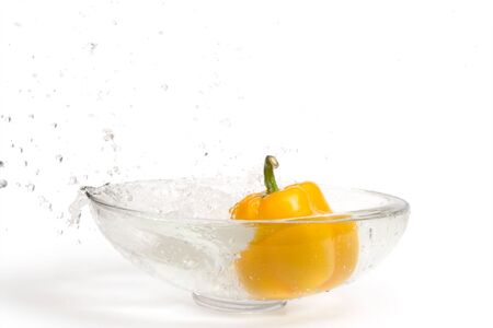 Yellow paprika falling into glass vase with water, splashes. Isolated over white photo