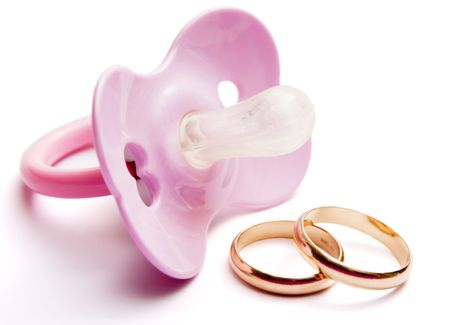 subdue:  pacifier and wedding rings, concept of having  after marriage, isolated, with clipping path